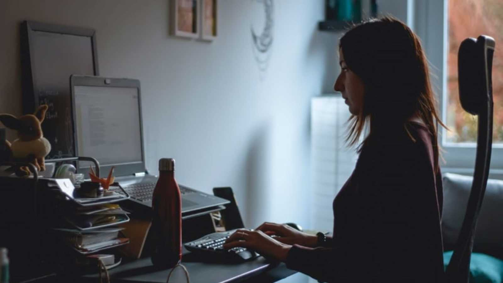 Woman types on a computer in the dark