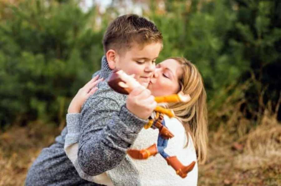 Special needs mom kisses son with autism holding Toy Story's Woody doll on cheek
