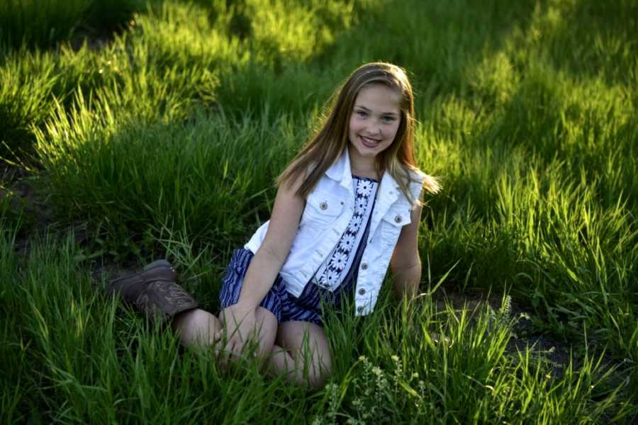 Girl with cowboy boots and white denim vest smiles in grass