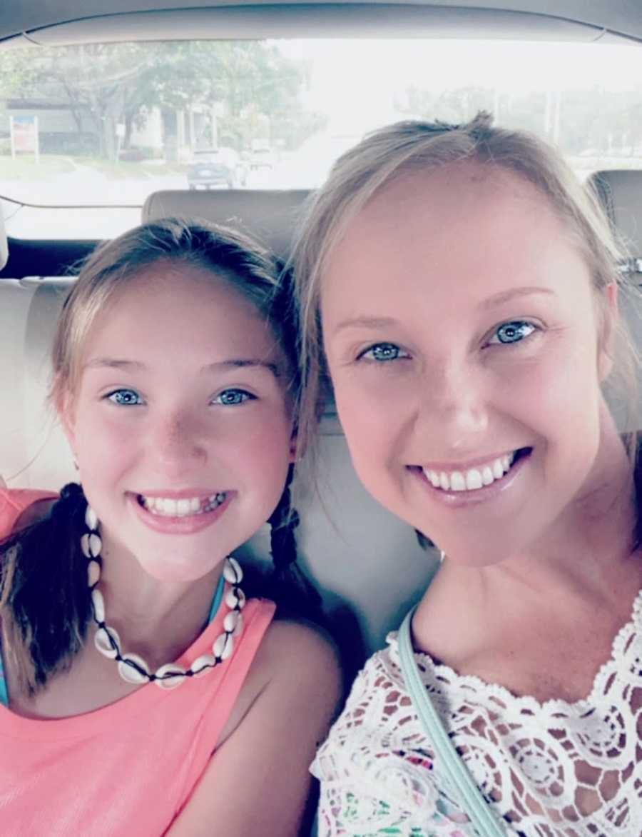 Mom and daughter smile for selfie in car seats
