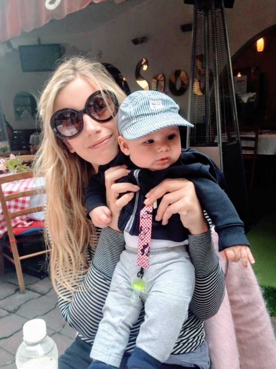 Teen mom in black sunglasses embraces son