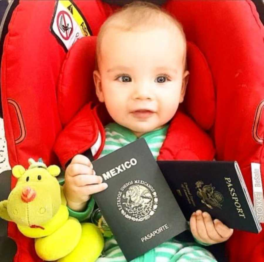 Infant in green footie pajamas holds Mexican passports