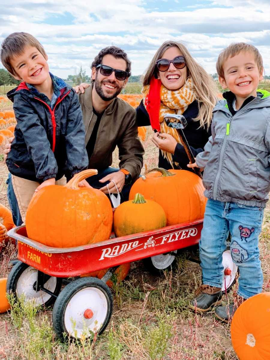 Teen mom with two sons and husband smile at pumpkin patch