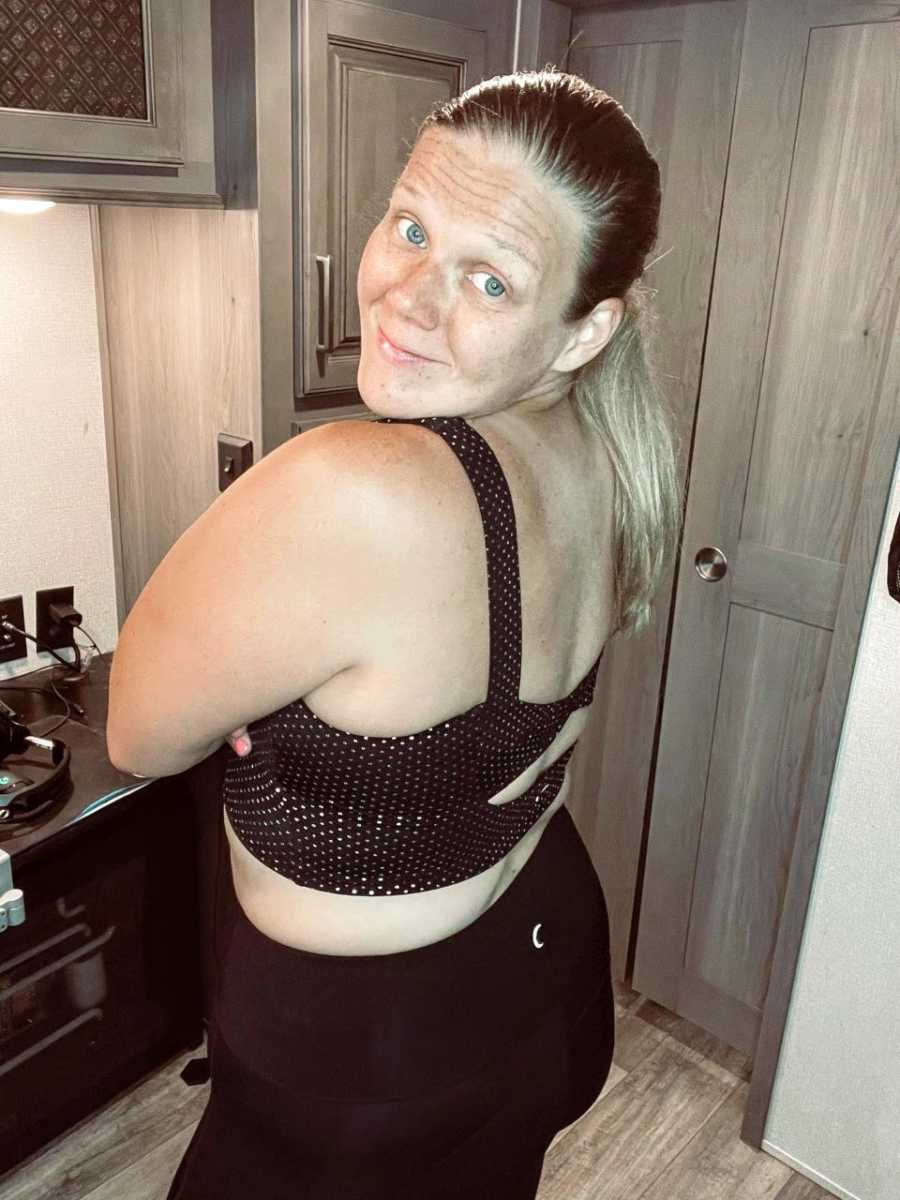 Plus-sized woman in black leggings and black crop top smiles for camera