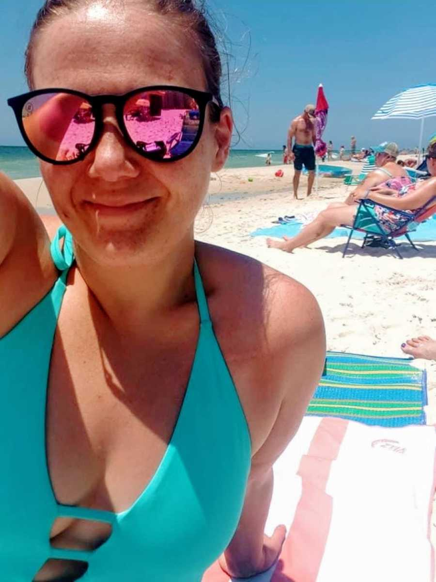 Woman in blue bathing suit and black sunglasses smiles in selfie on the beach