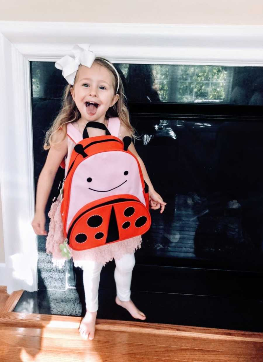 Girl with white bow smiles with ladybug backpack