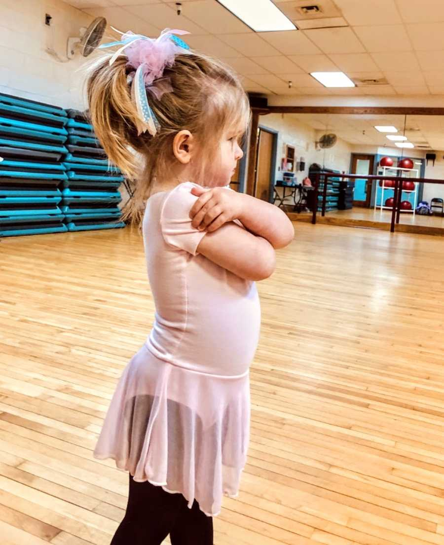 Girl in pink dress folds arms in ballet studio