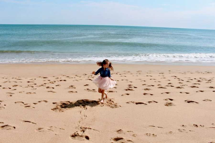 Girl in pink dress and jean jacket twirls on beach