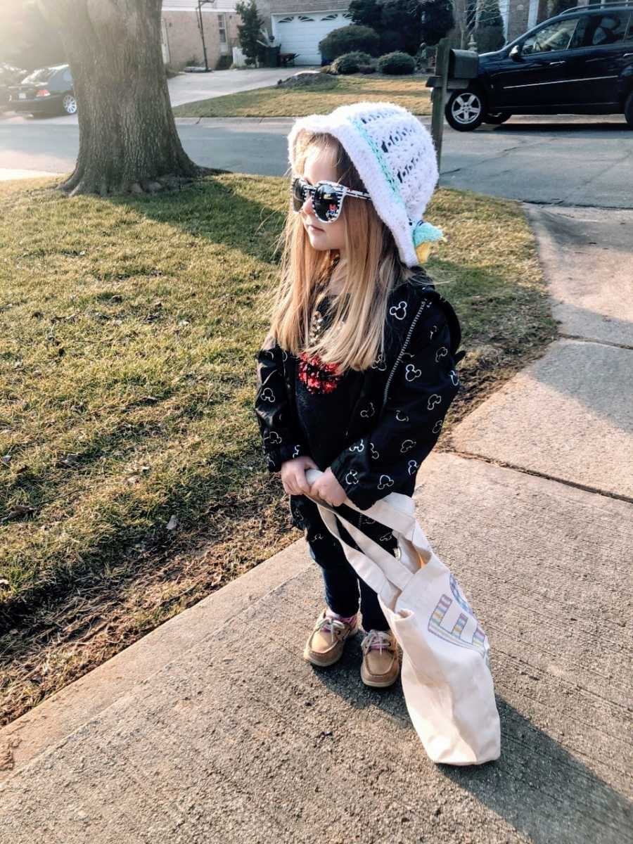 Girl with hat and sunglasses stands on sidewalk