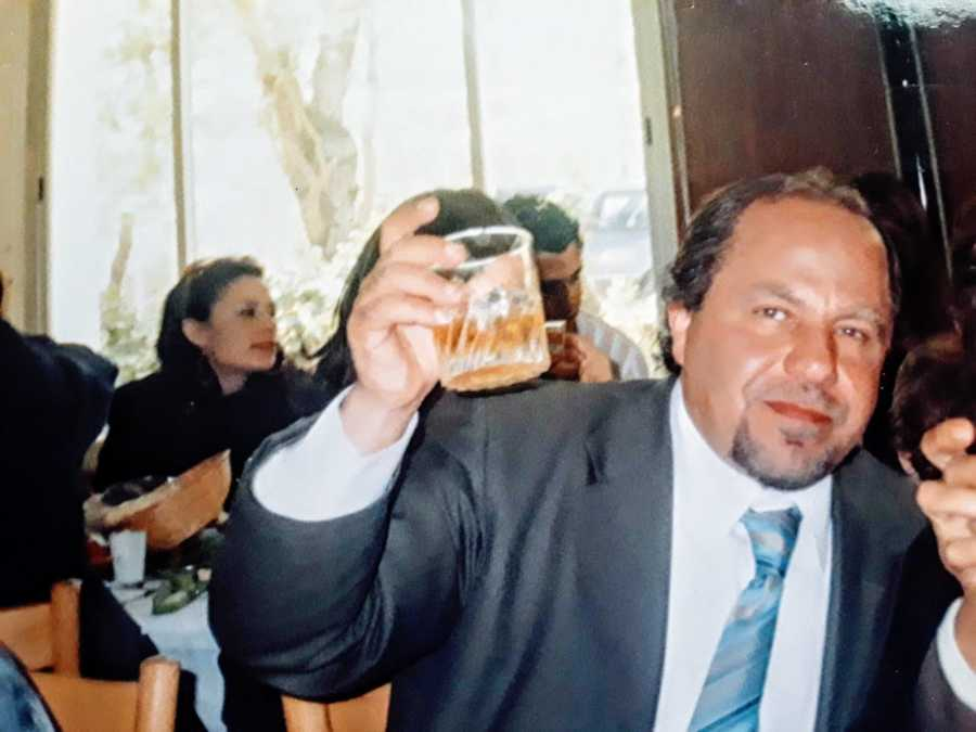 Man in suit battling addiction holds cup of alcohol
