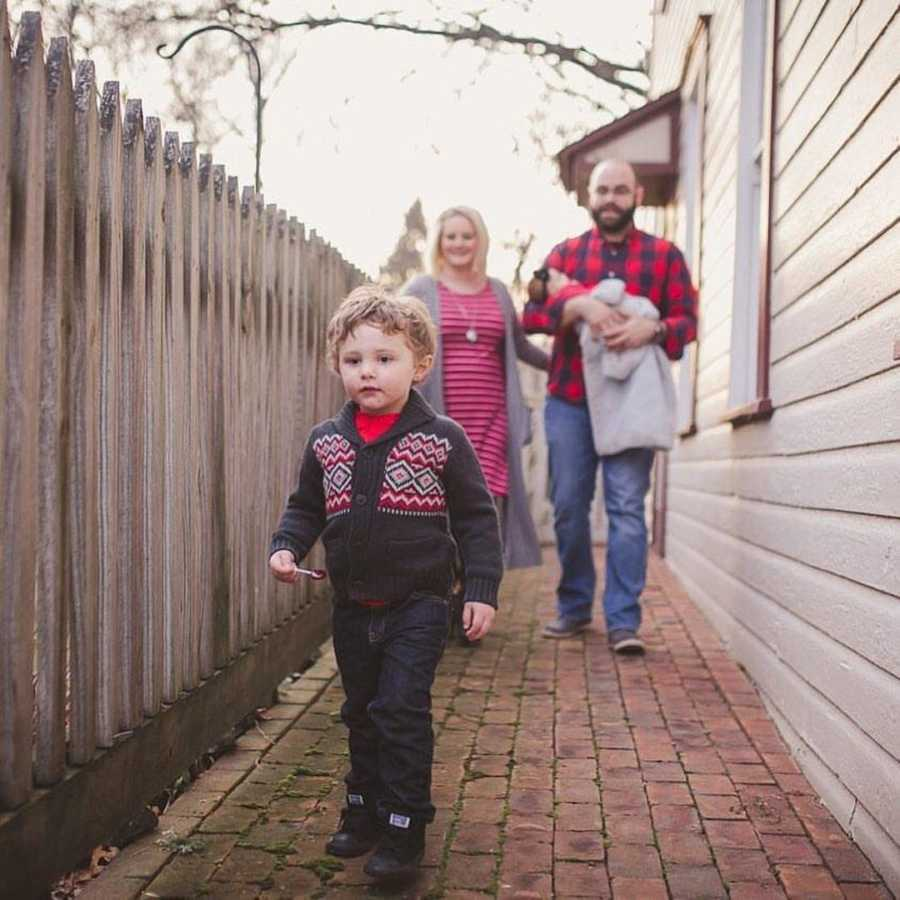 Special needs parents in red stand behind special needs son in red and grey sweater