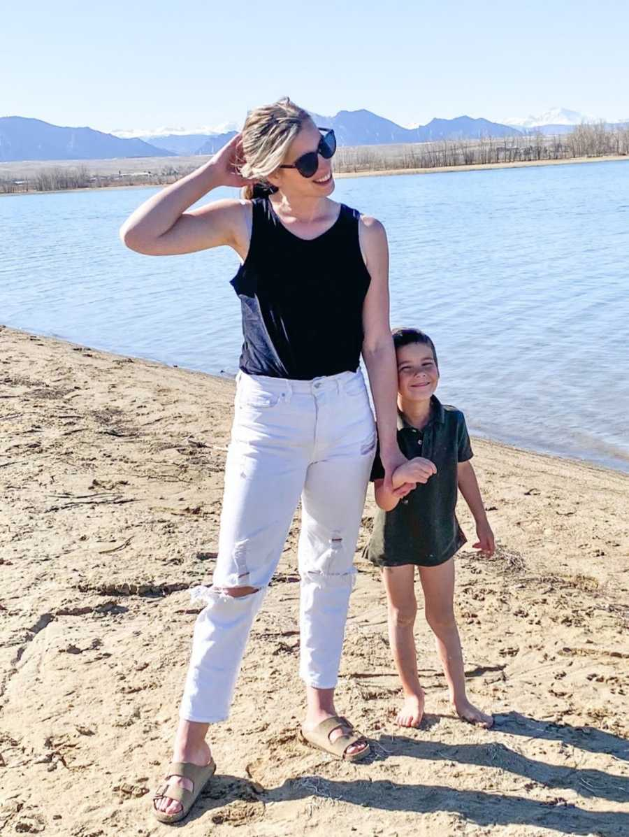 Teen mom in white pants holds son on beach