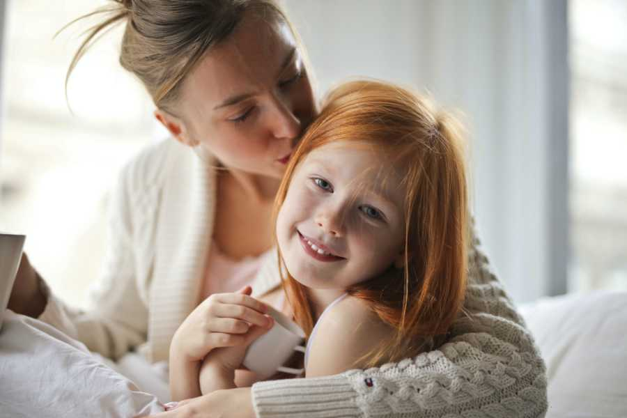 Blonde mom in white sweater with updo kisses daughter with red hair on head