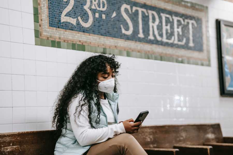 Woman with white face mask scrolls through phone on subway platform