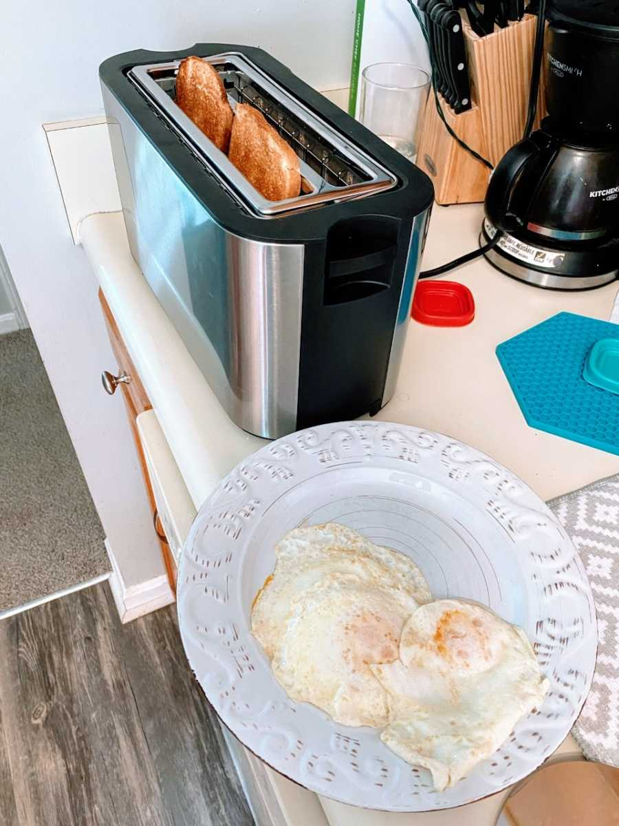 A mom shows off her breakfast of two fried eggs on a plate and two pieces of toast, still in the toaster