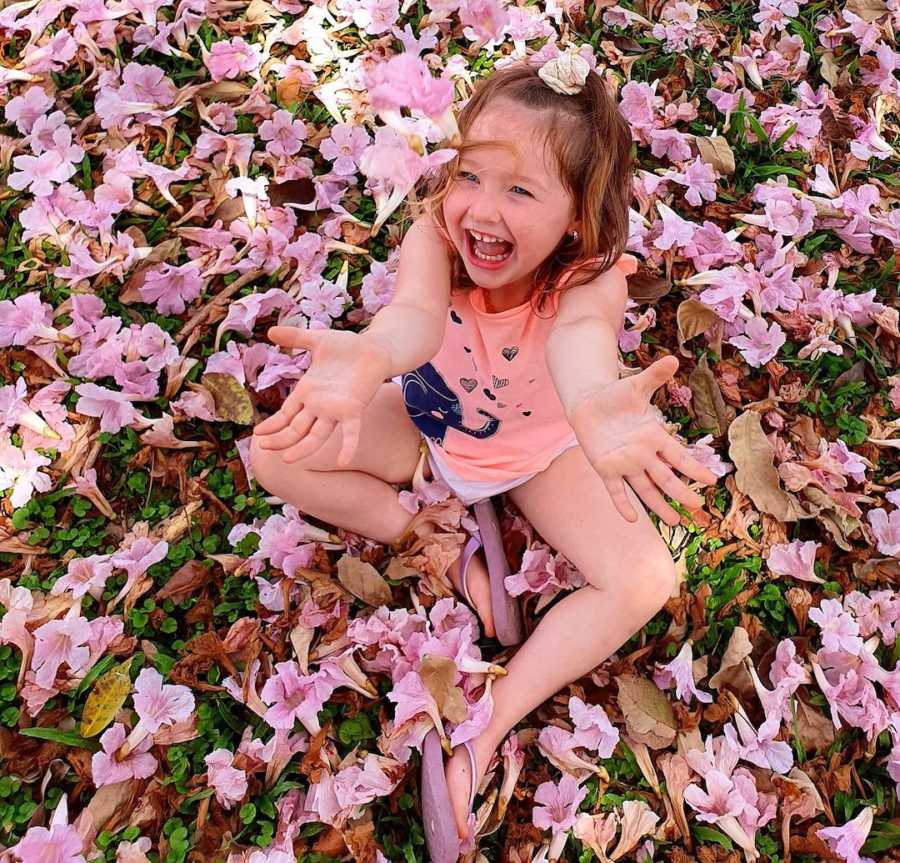 smiling young girl surrounded by flowers, outside
