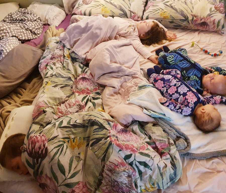 children all sleeping together on a mattress