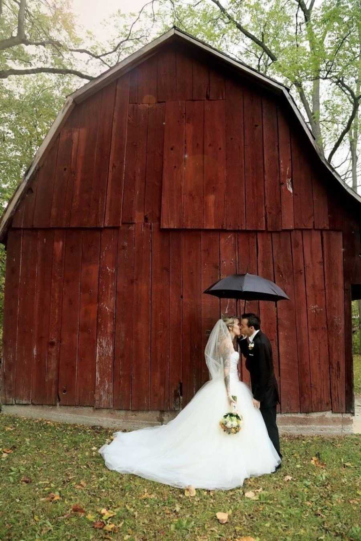 Wedding photos at barn with umbrella and wedding dress