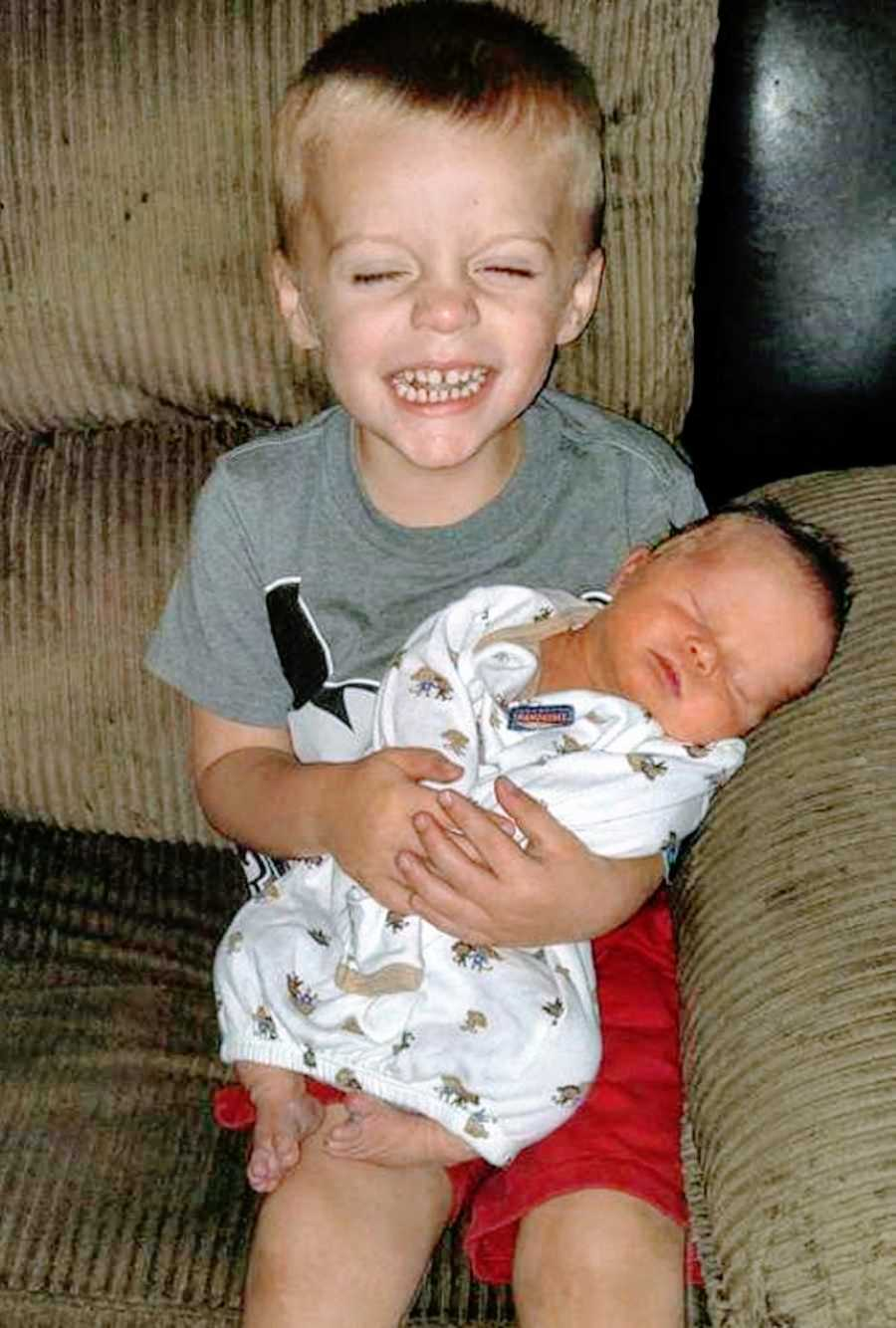 Little boy sitting on a brown couch holds newborn baby brother with a big smile