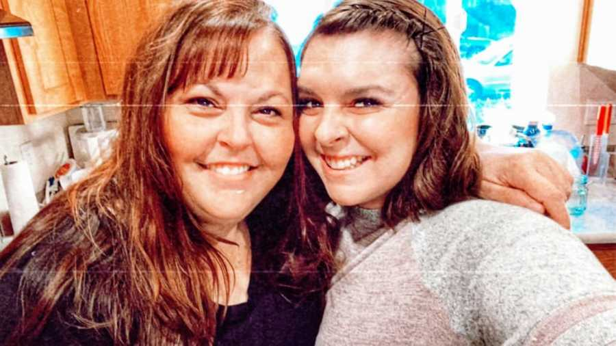 Woman smiles and takes selfie with mom in kitchen