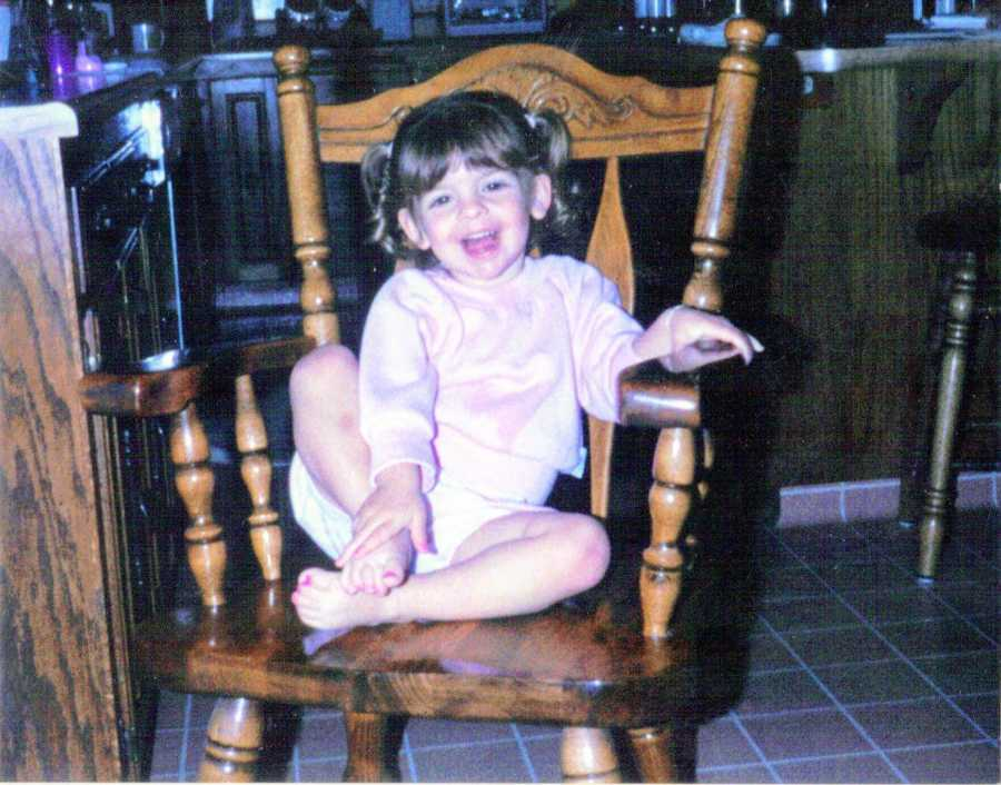 Young girl with pigtails smiles at camera while sitting in wooden chair