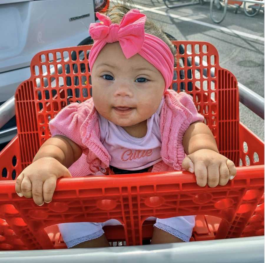 Baby girl wearing pink sitting in red grocery cart