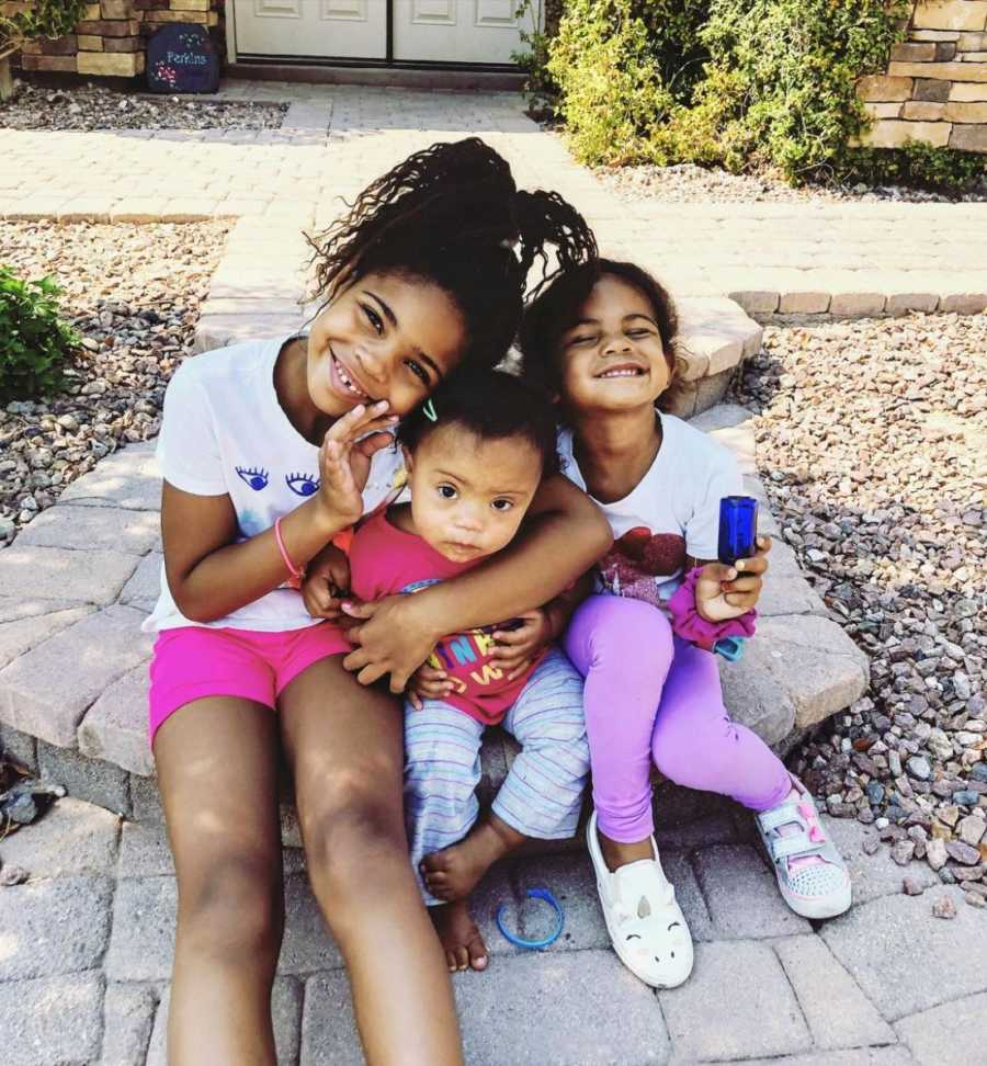 Three sisters hugging and smiling while sitting on sidewalk