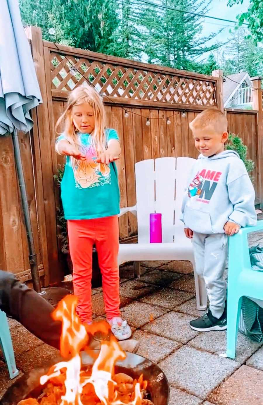 Two young kids stand outside and warm up by a fire in their backyard