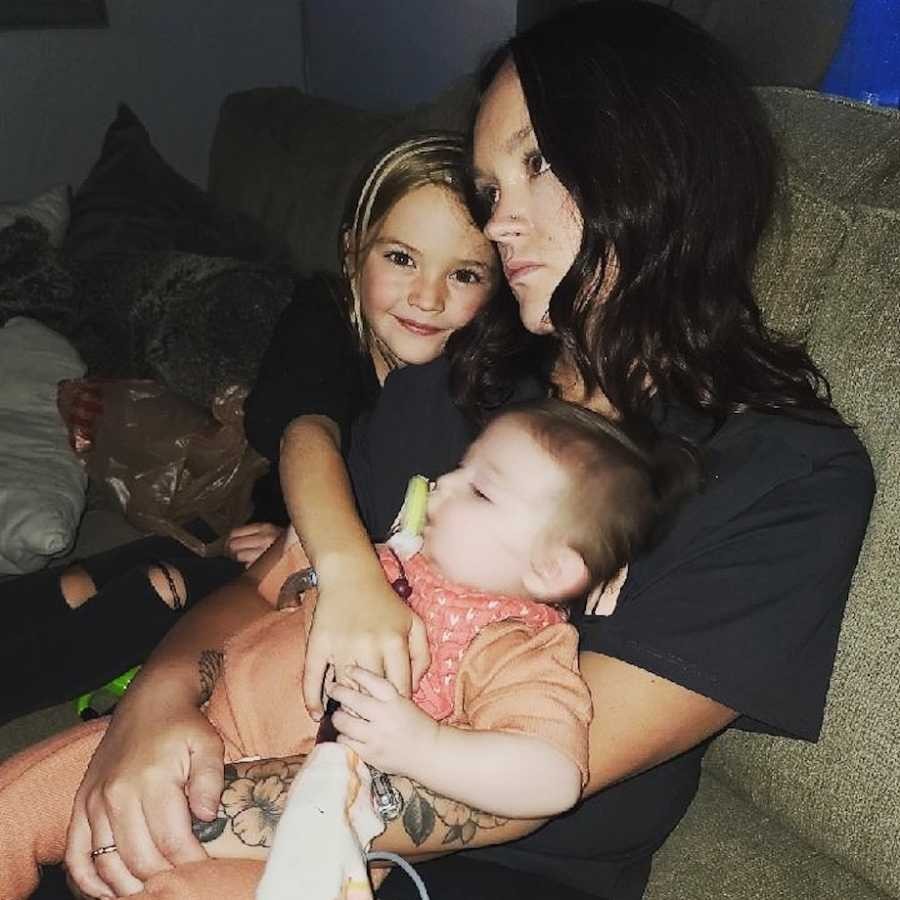 Mom holding daughters on couch