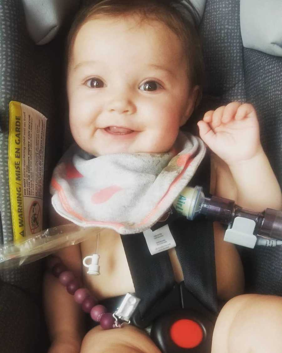 Baby with tracheostomy smiling in carseat
