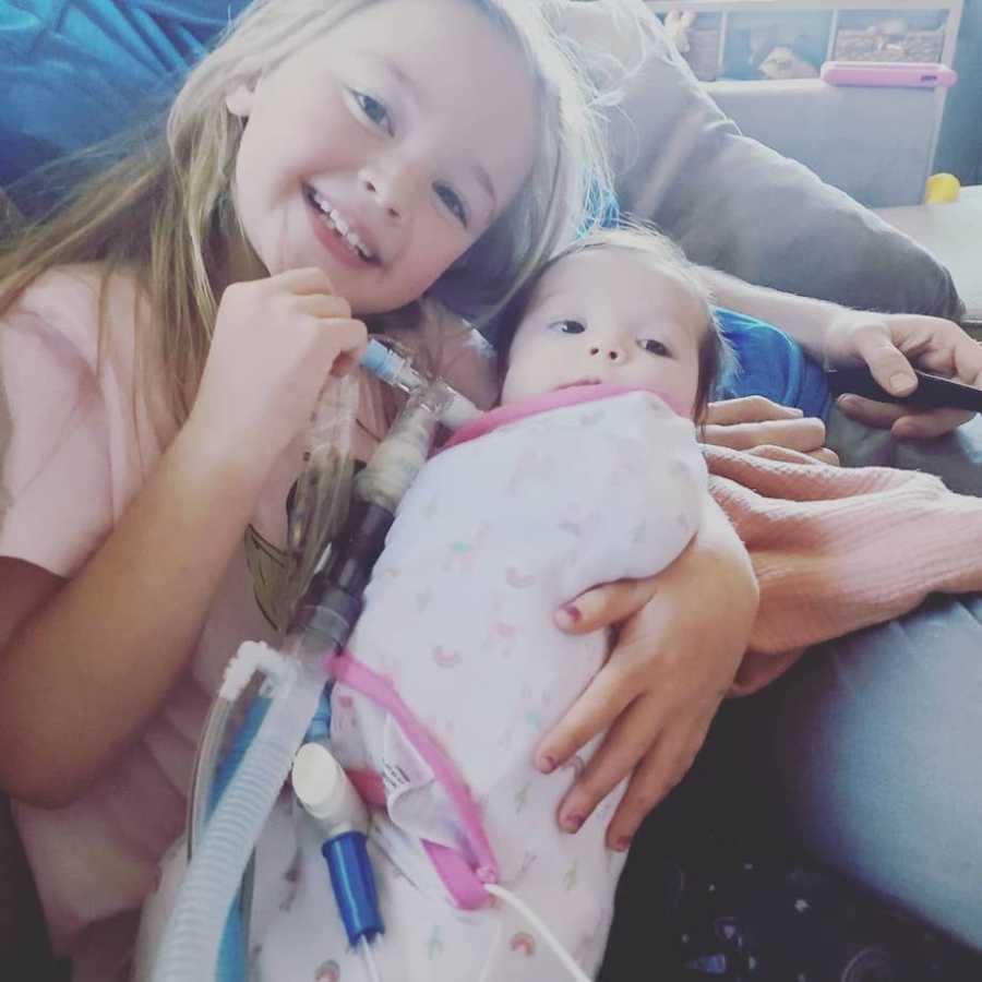 Sister holding newborn baby sister