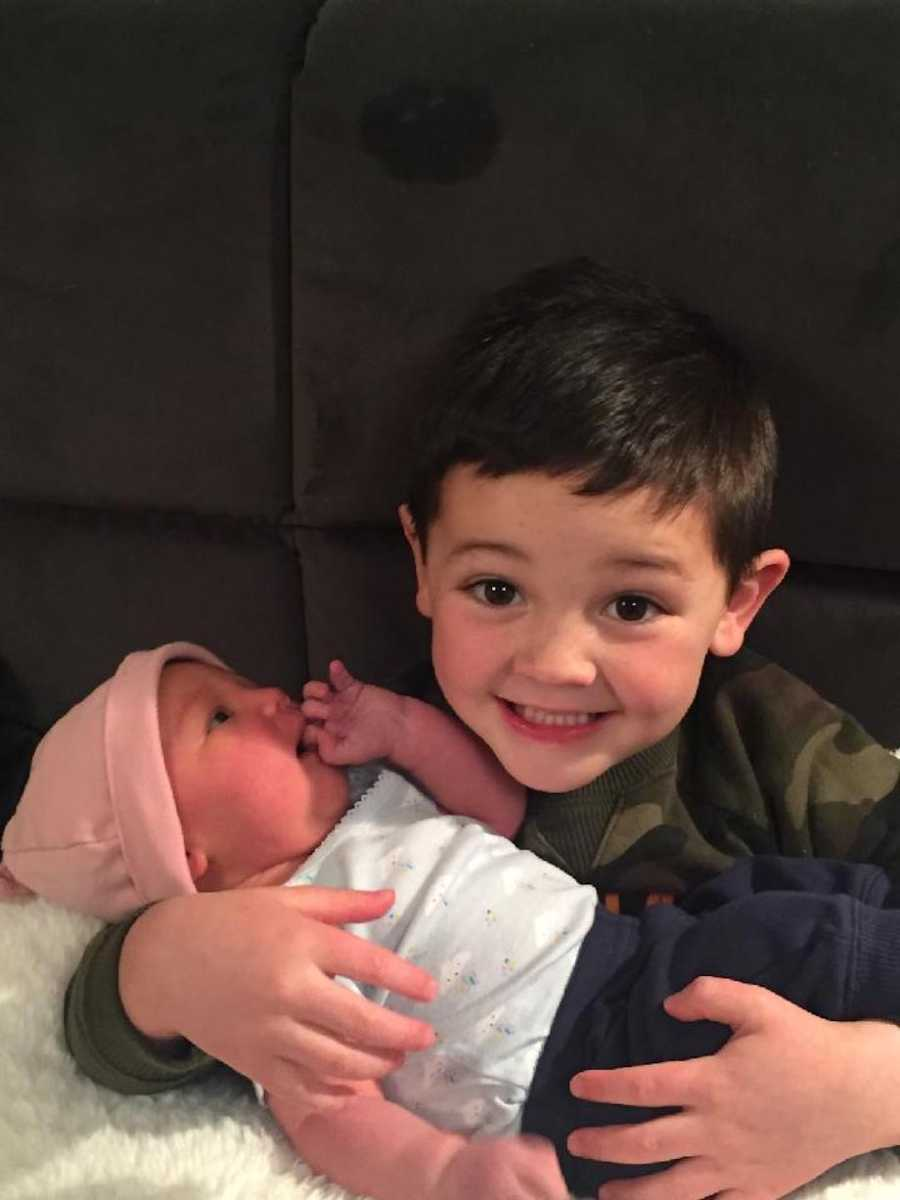 Brother holding newborn baby sister