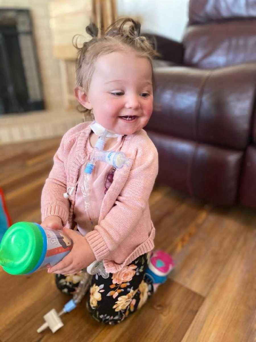 Baby with tracheostomy smiling and playing