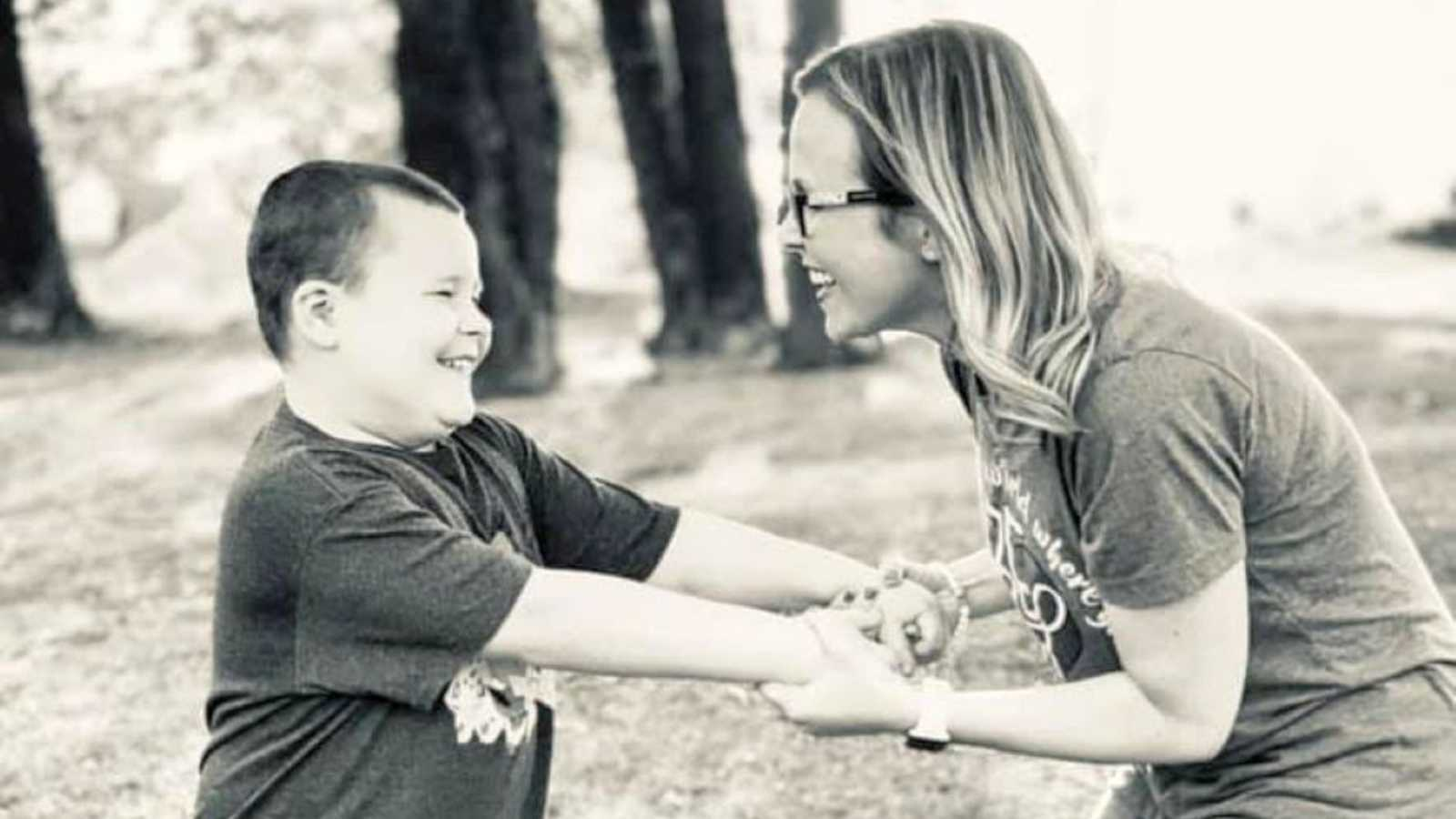 Boy mom smiles and holds hands with her autistic son during a family photoshoot