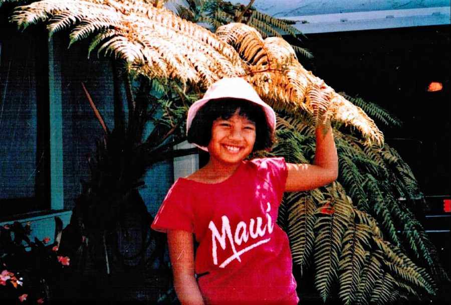 """Young girl in white bucket hat and a red shirt that says """"Maui"""" poses in front of a tree"""