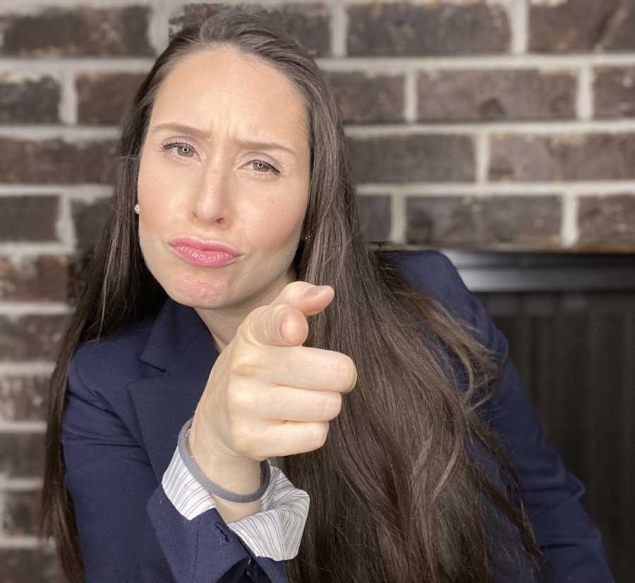 woman in suit pointing at camera