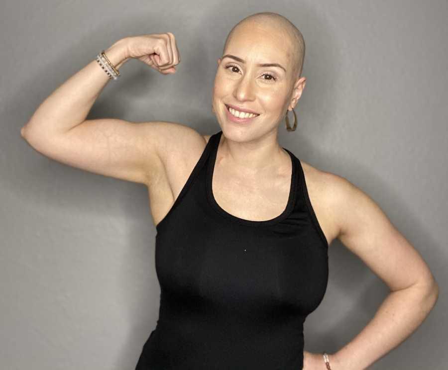 bald woman flexing arm