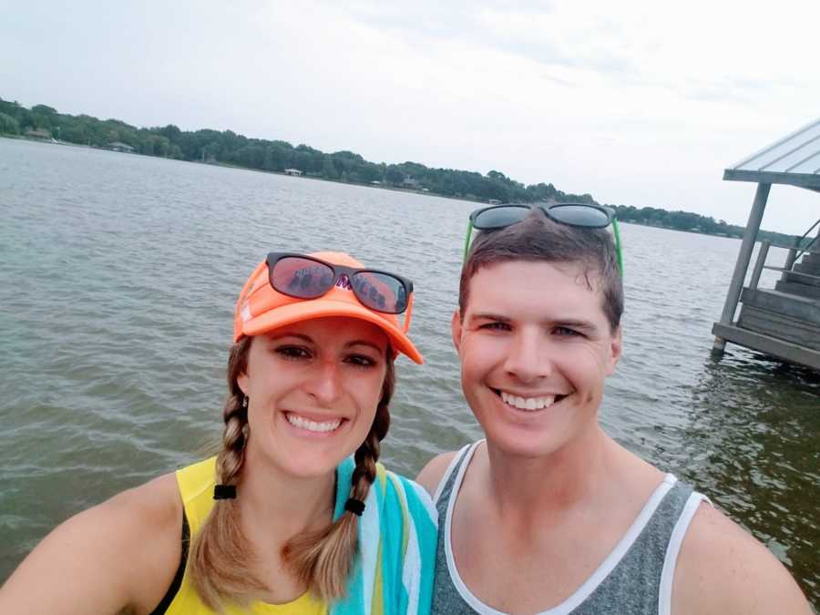 Couple smile and take a selfie in front of a lake in beach wear