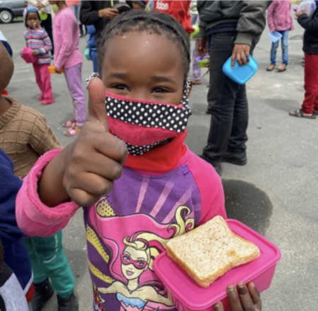 Little girl with mask giving a thumbs up
