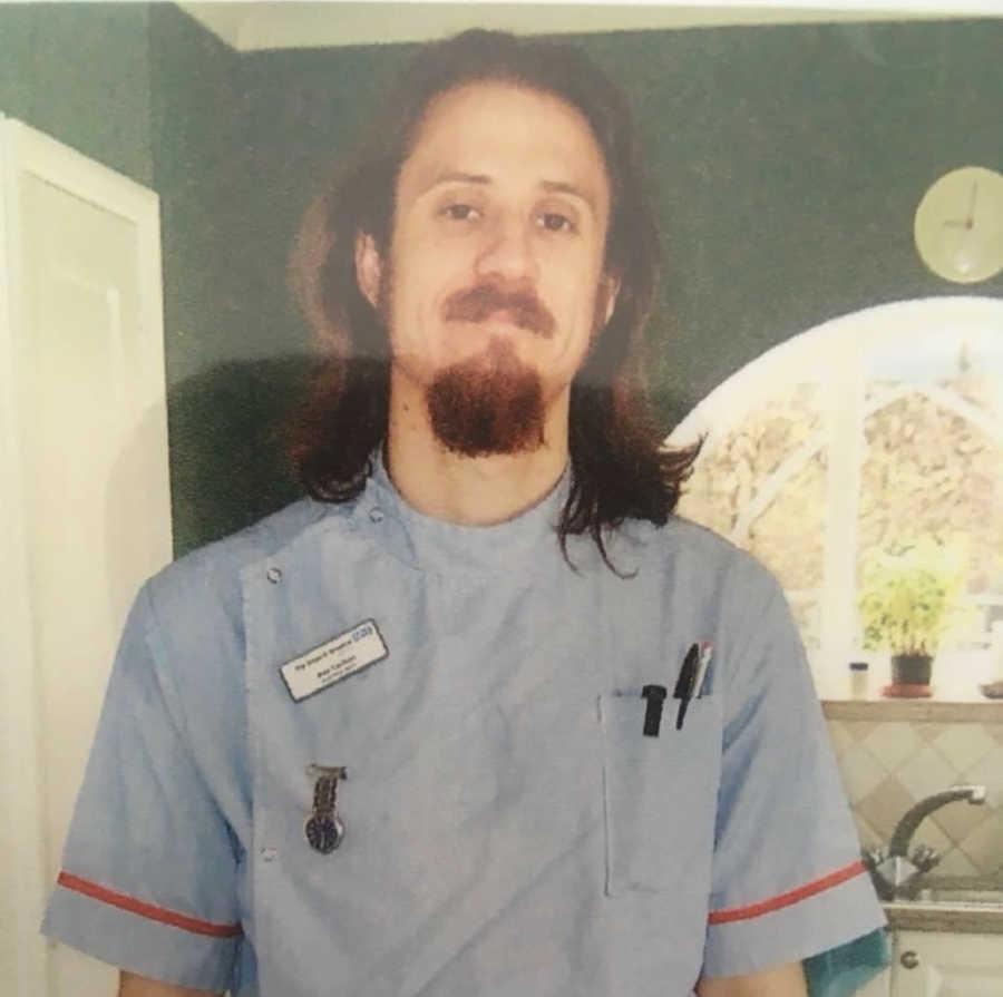Man with long hair and beard in nurses uniform
