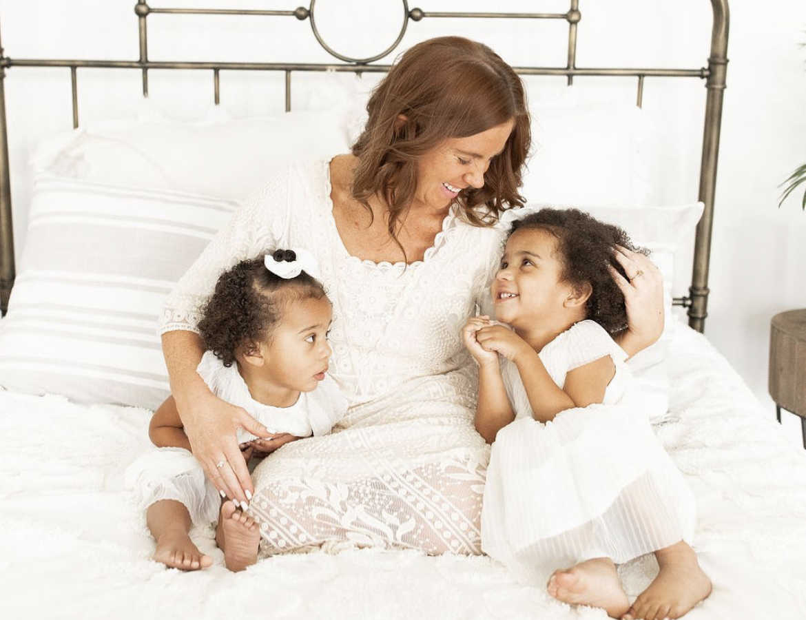 Mom with two mixed-race daughters sitting on bed smiling at each other