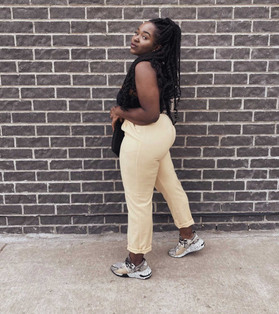 Body positive black woman poses in front of a brick wall.