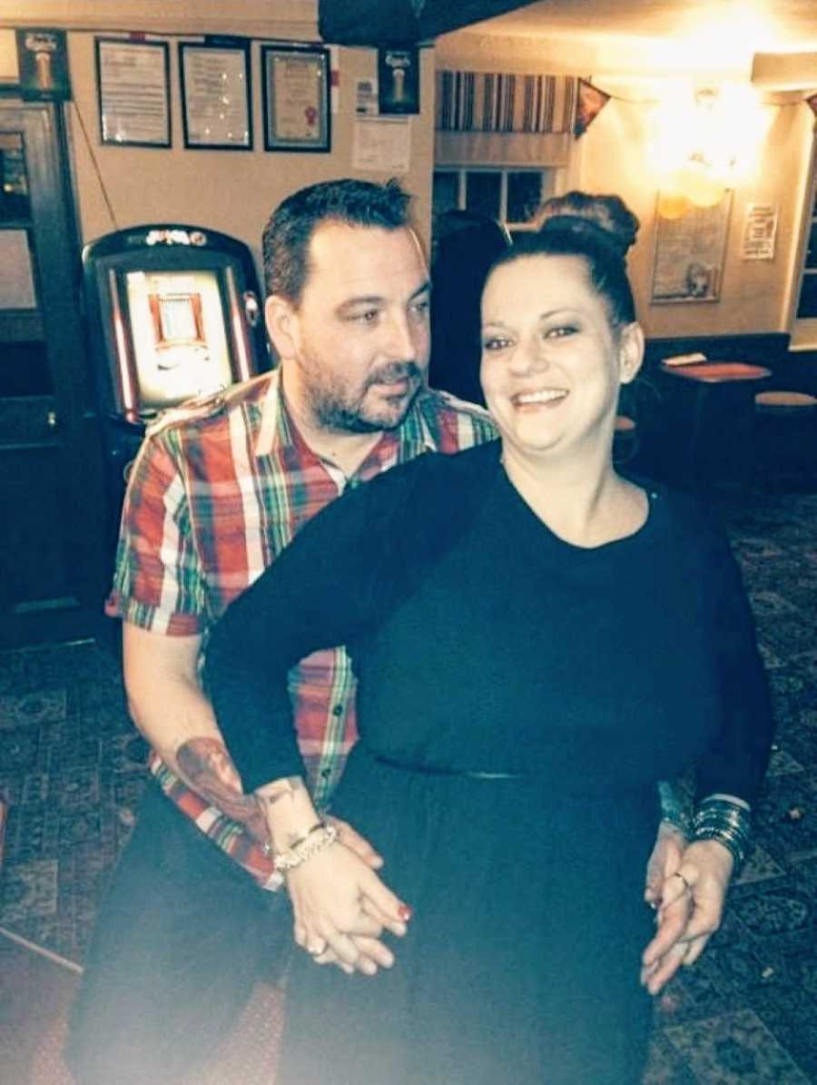 Tattooed couple pose for a photo together in a pub