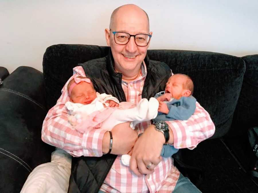 Grandfather proudly holds his newborn grandbabies, surprised by twins