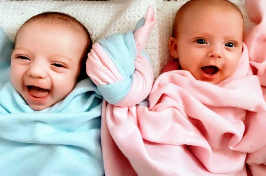 Newborn twins give the camera toothless smiles with their blankets tied together like a knot, representing their bond