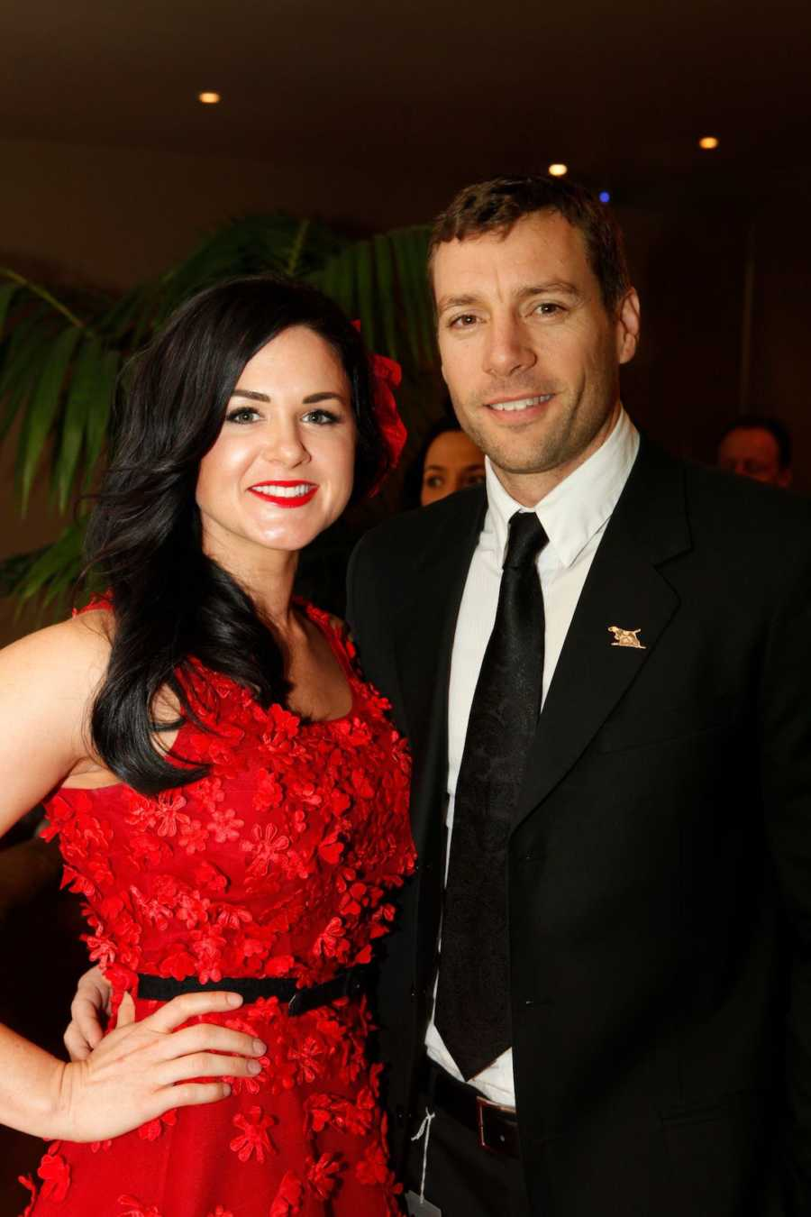Husband and wife wearing red dress smiling together