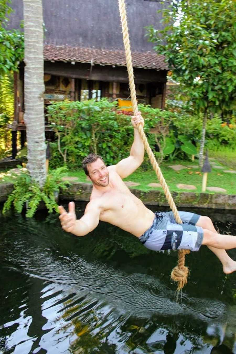 Man swinging on rope above body of water