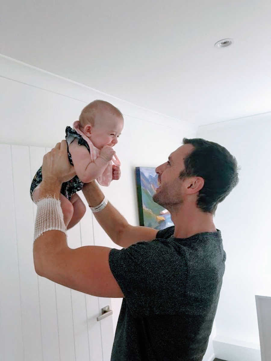 Father holding his smiling baby up in the air