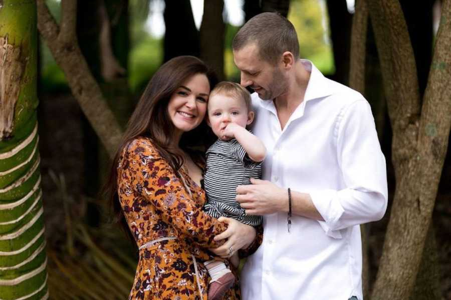 Husband and wife holding baby in front of trees