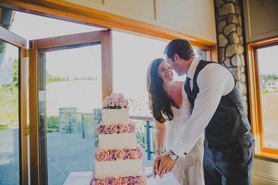 Newlywed couple cutting their wedding cake